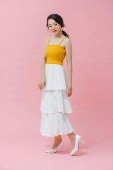 De foto van gemiddelde lengte van een jong aziatisch meisje met lang haar in een geel mouwloos onderhemd en een witte rok. op roze achtergrond.