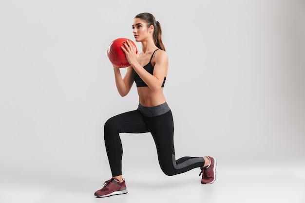 De foto van gemiddelde lengte van ernstige geconcentreerde sportvrouw die opzij kijkt en longeoefeningen met geschiktheidsbal doet, die over grijze muur wordt geïsoleerd