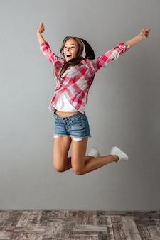 De foto van gemiddelde lengte van mooie jonge vrouw die in oortelefoons aan muziek luistert en springt