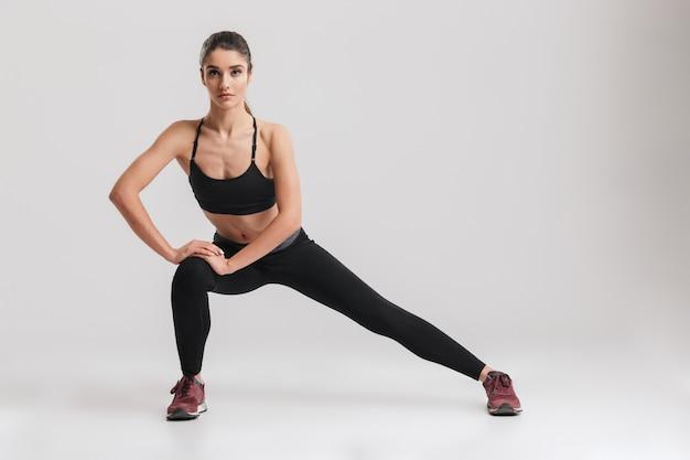 De foto van gemiddelde lengte van sportieve vrouw met haar in paardestaart die haar lichaam uitrekt en zijuitvaloefeningen doet, die over grijze muur worden geïsoleerd