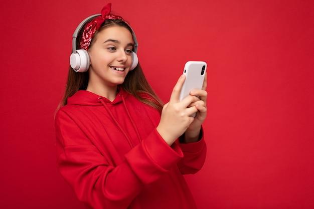 De foto van het close-upportret van mooi gelukkig glimlachend donkerbruin meisje die rode hoodie dragen die op rood wordt geïsoleerd
