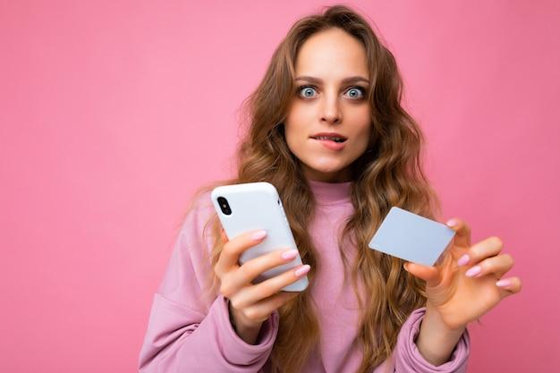 De foto van het close-upportret van vrij geschokt jonge blonde krullende vrouw die roze geïsoleerde kleren draagt