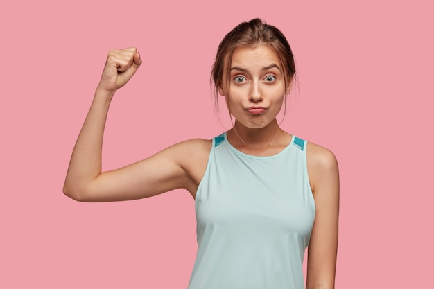 De foto van kaukasische sportvrouw toont spier, heft handen in vuist op