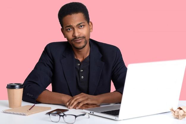 De foto van knap afrikaans amerikaans mannetje die rem van het werken met laptop computer nemen, heeft gezichtsuitdrukkingen die op roze worden geïsoleerd verstoord. mensen concept.