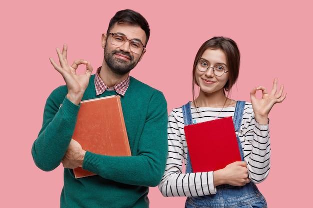 De foto van knappe mannelijke student en zijn vrouwelijke groepsgenoot toont ok gebaar, eens met iets