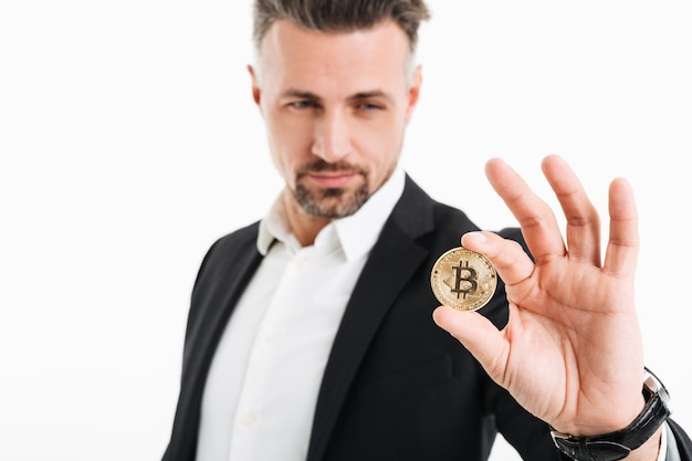 De foto van knappe rijke zakenman in kostuum die gouden bitcoin tonen concentreerde zich op camera, die over wit wordt geïsoleerd