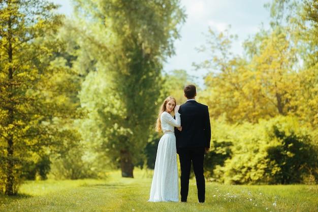 De foto van mooi enkel echtpaar die zich in parkbruid bevinden die de camera bekijken en de bruidegom heeft hem de rug toegekeerd.