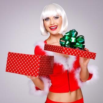 De foto van mooi sneeuwmeisje houdt de giftdoos van het kerstmisnieuwjaar