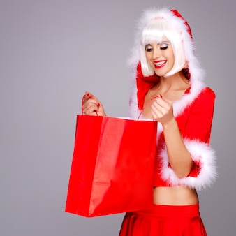 De foto van mooi sneeuwmeisje houdt het rode winkelen slecht