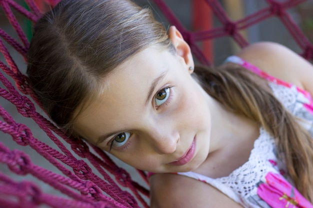 De foto van tienermeisje ligt op hangmat tijdens de zomerdag en bekijkt camera