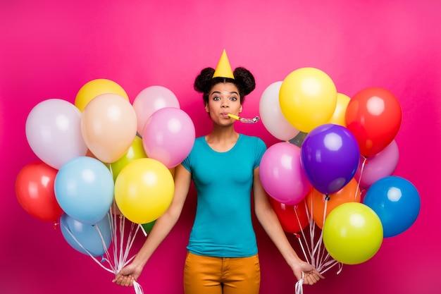 De foto van vrij grappige dame houdt vele kleurrijke luchtballons blaast noisemaker