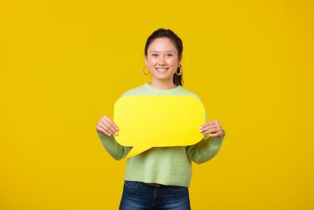 De foto van vrolijk jong meisje houdt een tekstbel op gele ruimte glimlachend bij de camera.
