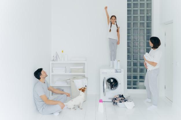 De foto van vrolijk meisje bevindt zich op wasmachine, heft wapen met gebalde vuist op