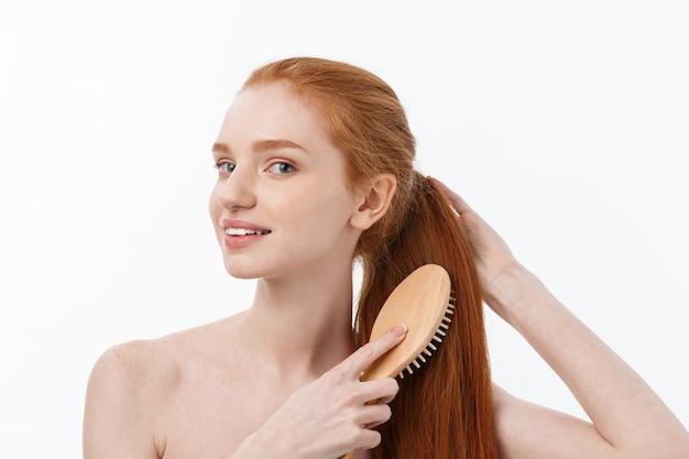 De foto van vrolijke glimlachende met sproeten gember jonge vrouw kamt haar lang rood haar