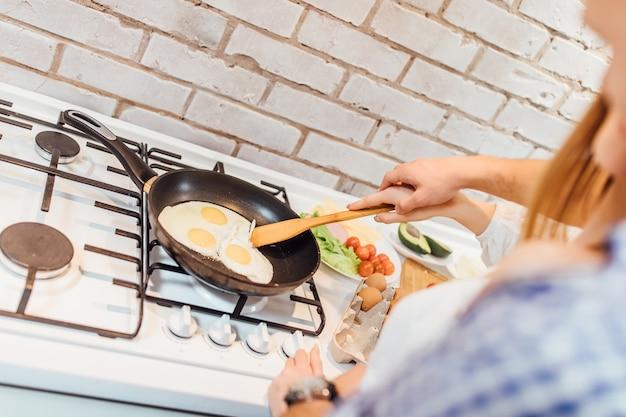 De foto van vrouw bakt een omlette op pan op fornuis. vrouw voorbereiding ontbijt eten