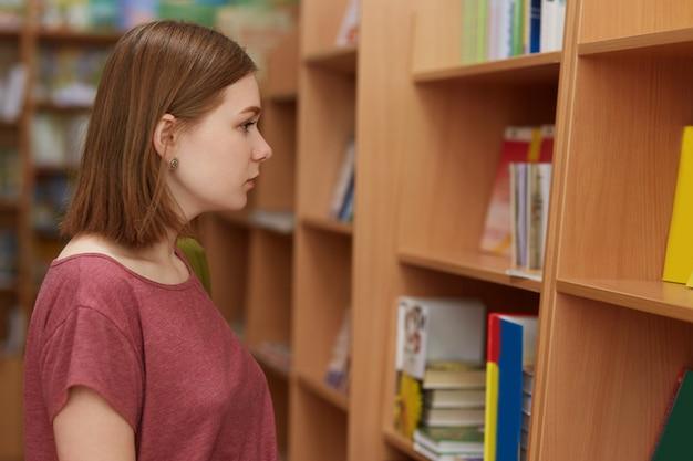 De foto van vrouwelijk kereltje stelt in boekhandel