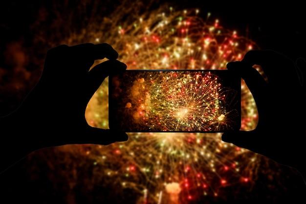 De foto van vuurwerk maken via smartphone. zend saluutvideo uit op internet.