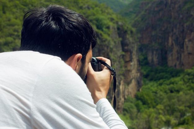 De fotograaf fotografeert de zonsondergang op de bergen