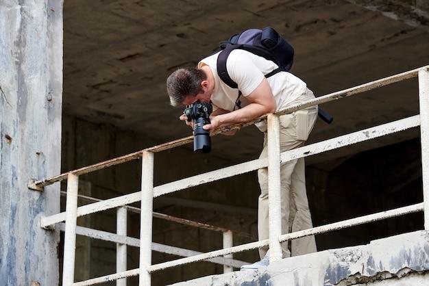 De fotograaf maakt foto op een verlaten gebouw.