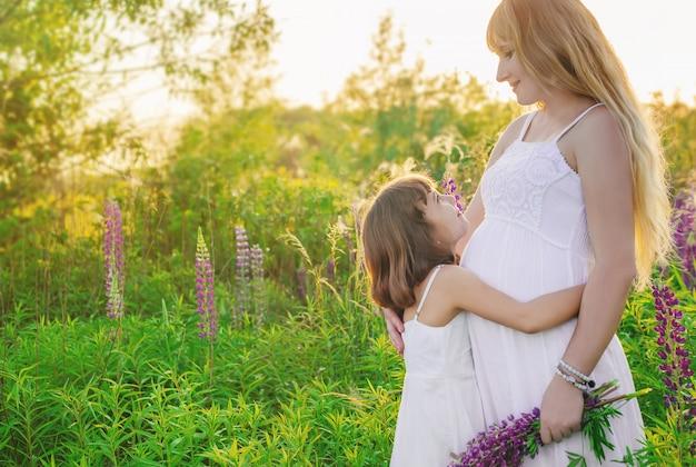 De fotosessie van het kind in een lupineveld met een zwangere moeder