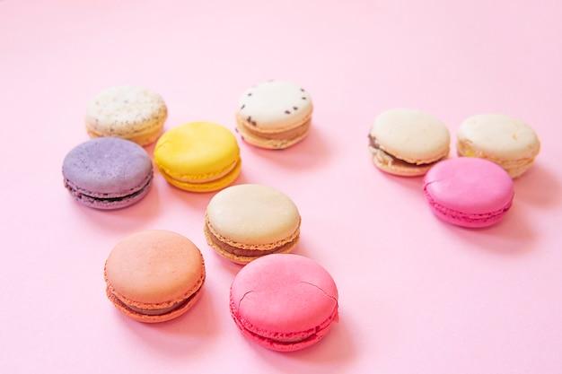 De franse kleurrijke vlakte van makaronscakes legt geïsoleerd op roze achtergrond
