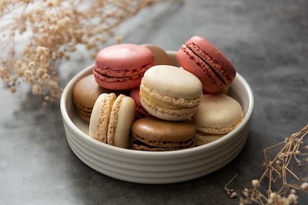De franse macaroncakes in een plaat sluiten omhoog. crème, bruin, roze, macarons met kopie ruimte.