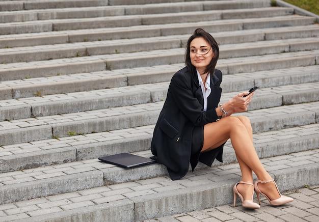 De freelancer is een ondernemer met een laptop op de trap, ze heeft pauze