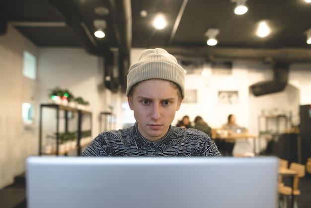 De freelancer werkt voor een laptop in een gezellig café. een jonge echtgenoot hipster gebruikt een computer in een café voor een kopje koffie.