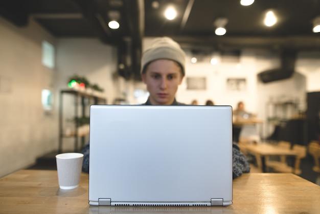 De freelancer werkt voor een laptop in een gezellig café. een student gebruikt een laptop in een café. focus op de laptop.