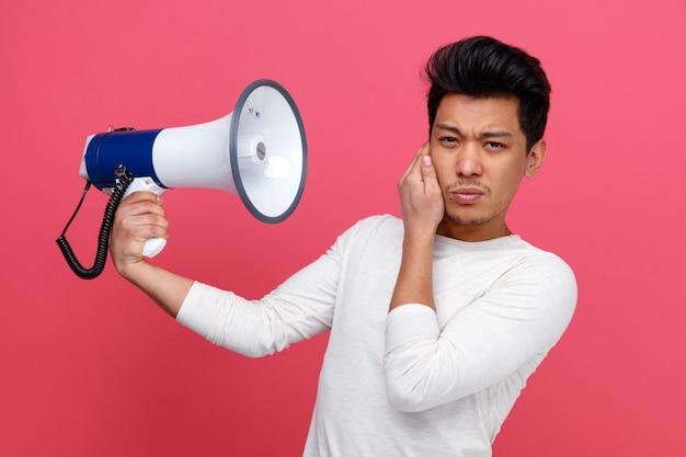 De fronsende spreker van de mensenholding die hand op oor houden