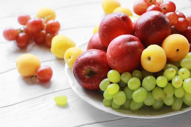 De fruitperziken, abrikozen, appelen en druiven in een witte plaat op een witte houten lijst sluiten omhoog