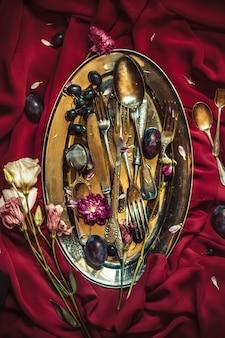 De fruitschaal met druiven en pruimen in verzilverd tafelgerei