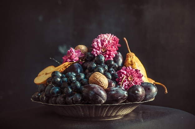 De fruitschaal met druiven en pruimen tegen een donkere muur