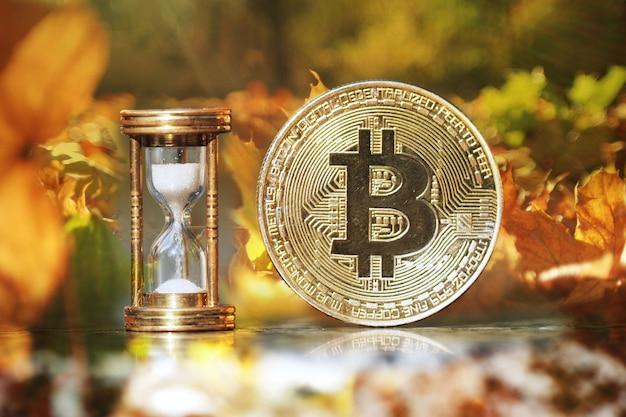De fysieke bitcoin en zandloper laten zien dat de tijd komt en de herfst is aangebroken