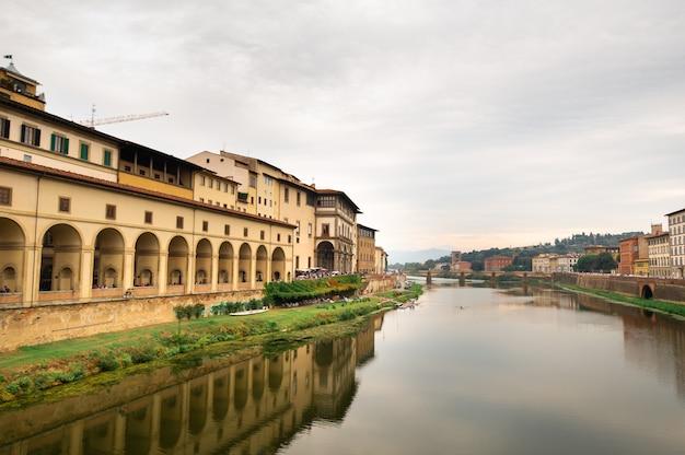 De galleria degli uffizi en de rivier de arno uit de ponte vecchio-brug over de rivier de arno in florence, italië.
