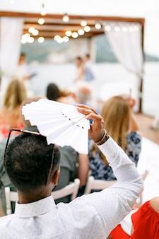 De gast bij de huwelijksceremonie zit dekens van de zon en fantaseert over zichzelf met een witte waaierrug