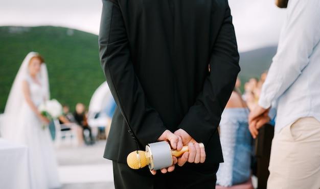De gastheer op een huwelijksfeest staat op en houdt een microfoon achter zijn rug