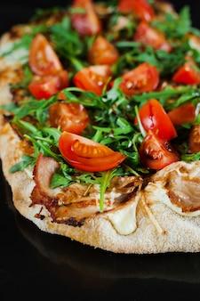 De gastronomische italiaanse keuken van pinsa romana op zwarte achtergrond. scrocchiarella. pinsa met vlees, rucola, tomaten, kaas.