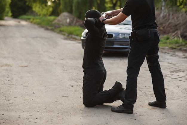 De gearresteerde dader knielt en de politieman draagt hem geboeid. wet en orde.