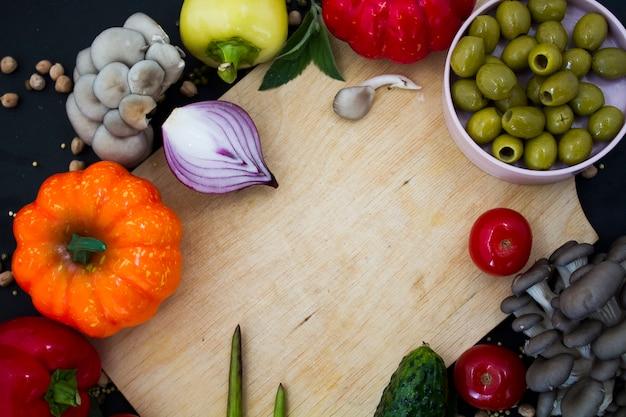 De geassorteerde groenten die op het koken worden voorbereid liggen op een houten lijst