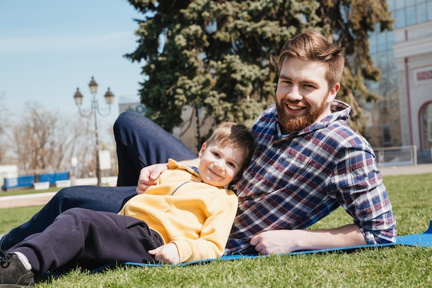 De gebaarde gelukkige vader ligt in openlucht met zijn zoon in park