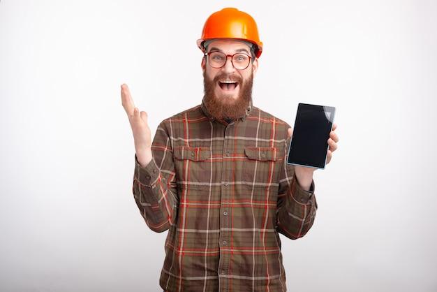 De gebaarde ingenieur die glazen en bouwvakker dragen is opgewekt over het werken met een tablet op witte ruimte.
