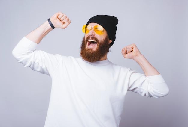 De gebaarde jonge mens in wit schreeuwt met beide handen omhoog, gele glazen en een zwarte hoed op witte muur.