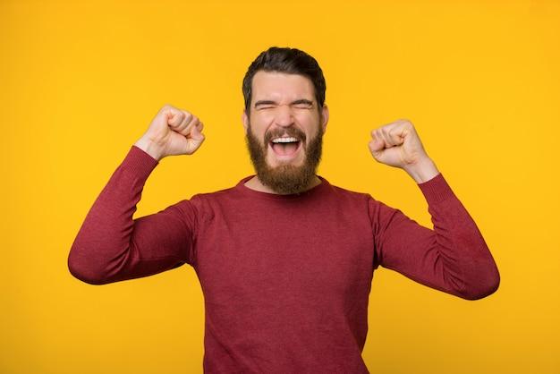 De gebaarde jonge mens schreeuwt van vreugde met beide handen omhoog dichtbij gele achtergrond.