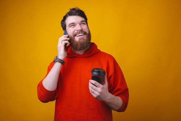 De gebaarde kerel spreekt op de telefoon terwijl het genieten van van hem koffie op gele ruimte weghaalt.