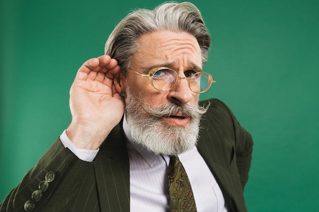 De gebaarde leraar van middelbare leeftijd in kostuum houdt oor en luistert op groene muur af