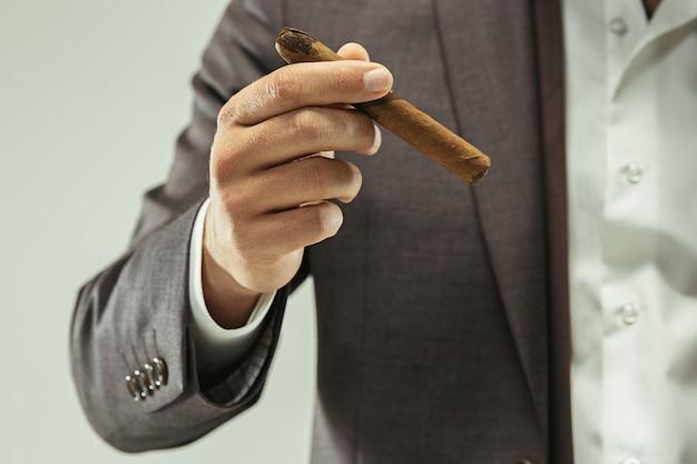 De gebaarde man in een pak met sigaar