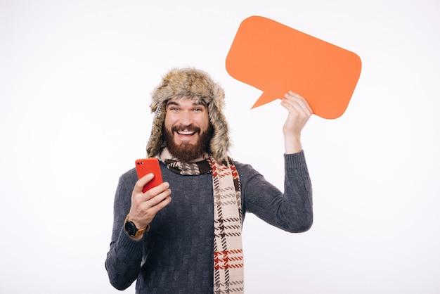 De gebaarde mens met een sjaal en een hoed, houdt een telefoon en een bellentoespraak op een witte achtergrond.