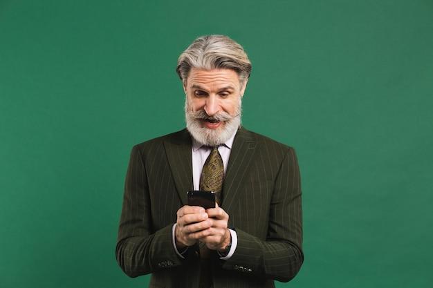De gebaarde mens op middelbare leeftijd in kostuum bekijkt telefoon en toont schok op groene muur
