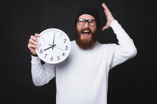 De gebaarde mens schreeuwt en houdt een groot horloge op zwarte muur.